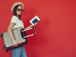 happy female traveler with suitcase on red background