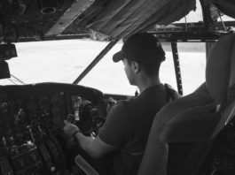 grayscale photo of man flying a plane