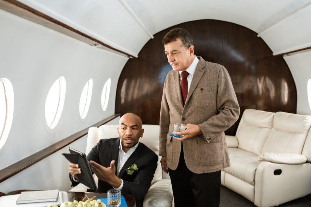 man in brown suit jacket standing beside man in black suit